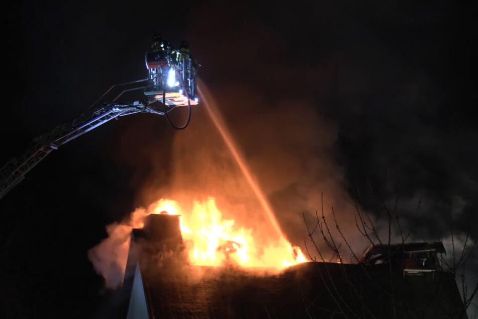 Von der Drehleiter aus versuchen Feuerwehrleute, den Hausbrand zu löschen.