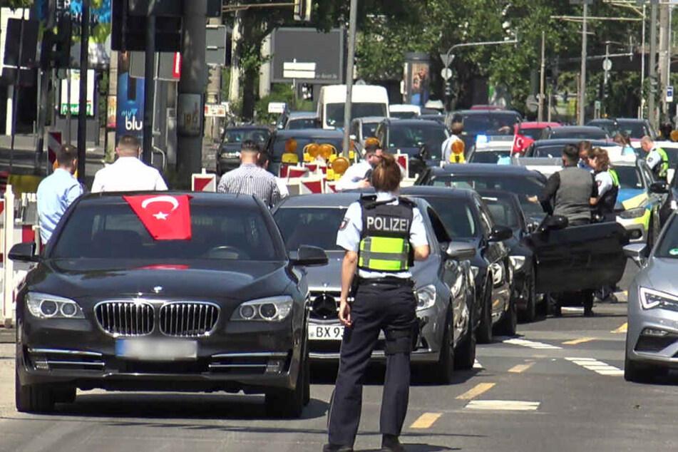 Eine Polizistin steht vor den Fahrzeugen eines türkischen Hochzeitskorsos.