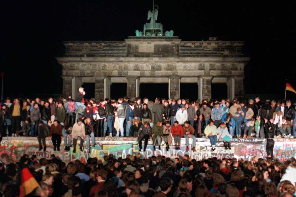 Jubelnde Menschen sitzen 1989 auf der Berliner Mauer.