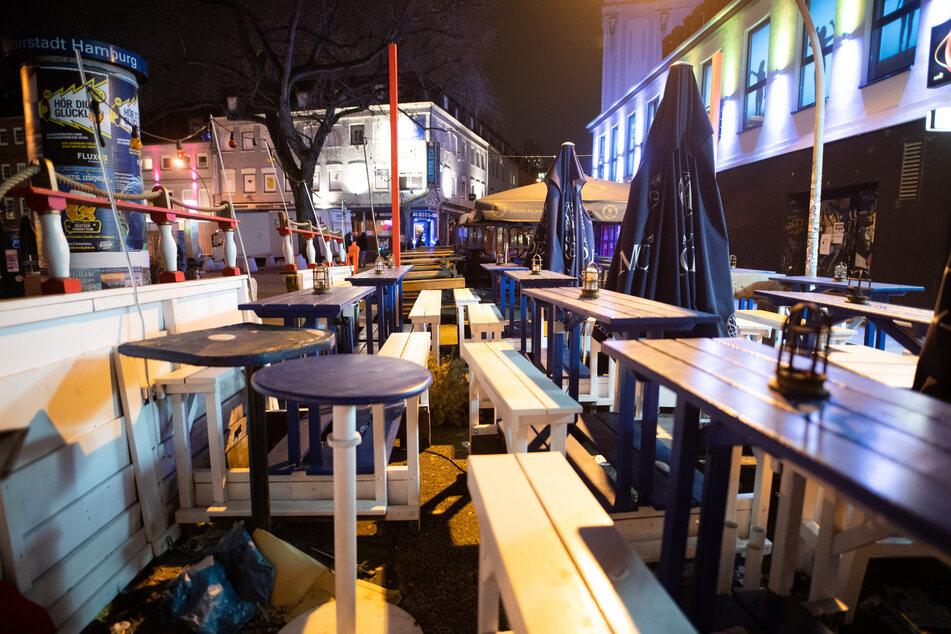 Leere Tische und Bänke stehen vor einem Club auf dem Hamburger Kiez