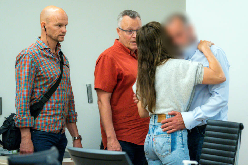 Der Angeklagte (r) wird in einer Pause der Verlesung des Urteils von seiner Freundin umarmt, während eine Spezialeinheit der Polizei (M) neben ihm steht.