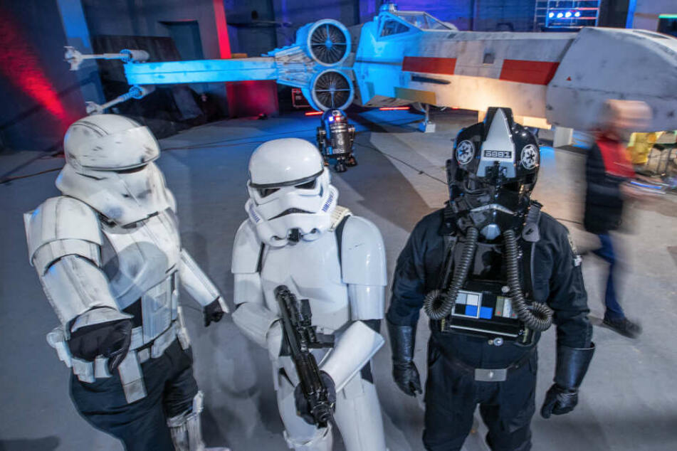 """Verkleidete Star-Wars-Fans stehen stehen vor dem Nachbau der """"X-Wing""""."""
