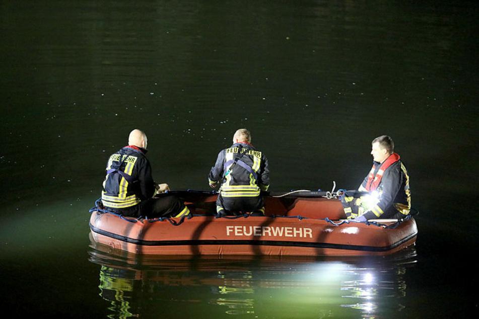 Feuerwehrleute suchen im Licht von Scheinwerfern im Elsterflutbett nach dem von der Brücke gestürzten Mann.