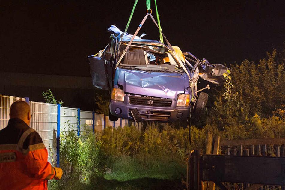 Das Fahrzeugwrack wird nach dem Zusammenstoß aus einem Gebüsch auf ein Bergungsfahrzeug gehoben.
