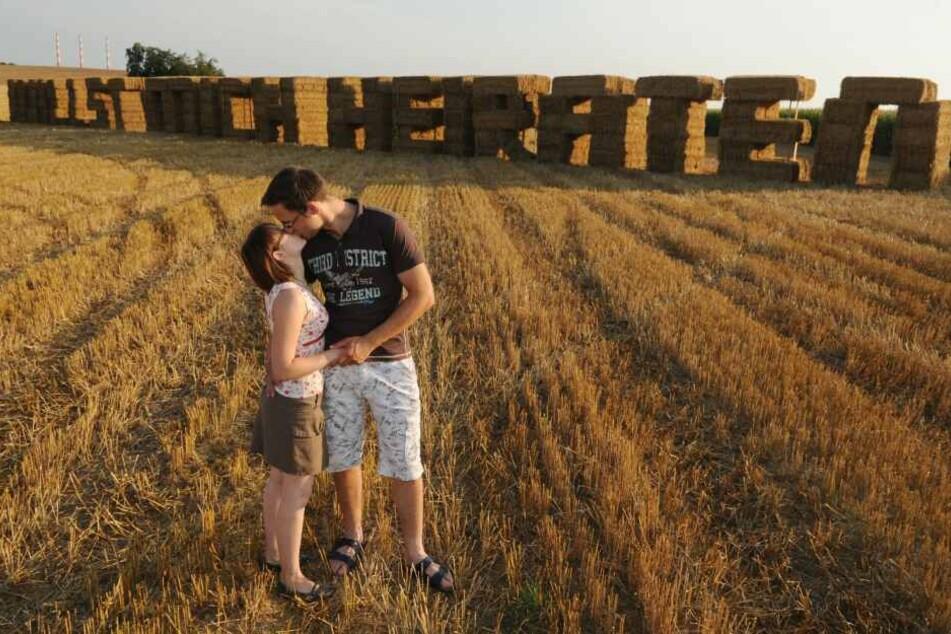 """Markus Schmidt küsst am Freitag (22.08.2009) in Pettling (Oberbayern) auf Strohballen seine Verlobte Corinna Pesl vor den aus Strohballen errichteten Worten """"Willst mich heiraten""""."""