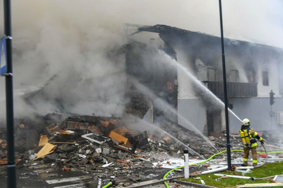 Ein Feuerwehrmann löscht den entstandenen Brand nach der Explosion.