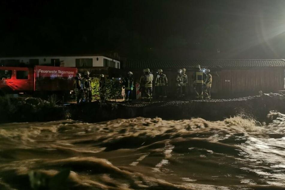 Feuerwehrleute sichern in der Nacht von Sonntag auf Montag einen Damm an der Rottach zwischen Rottach-Egern und Tegernsee. Durch den starken Regen seit Sonntagnachmittag führte die Rottach kurzfristig mehr Wasser.