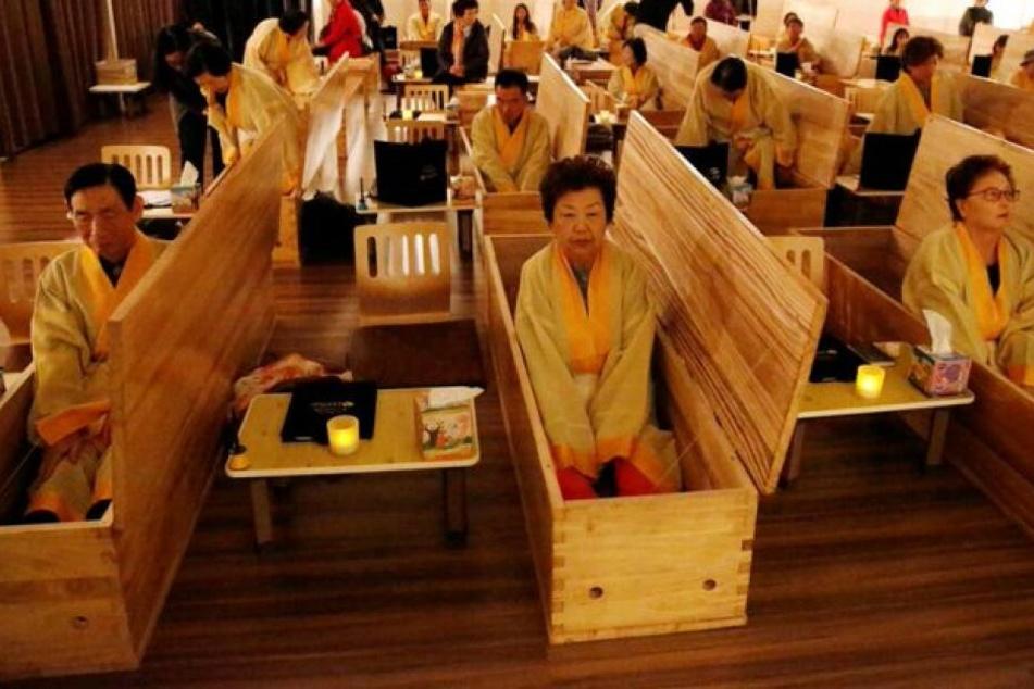 Teilnehmer sitzen in ihren Särgen, die später verschlossen werden.