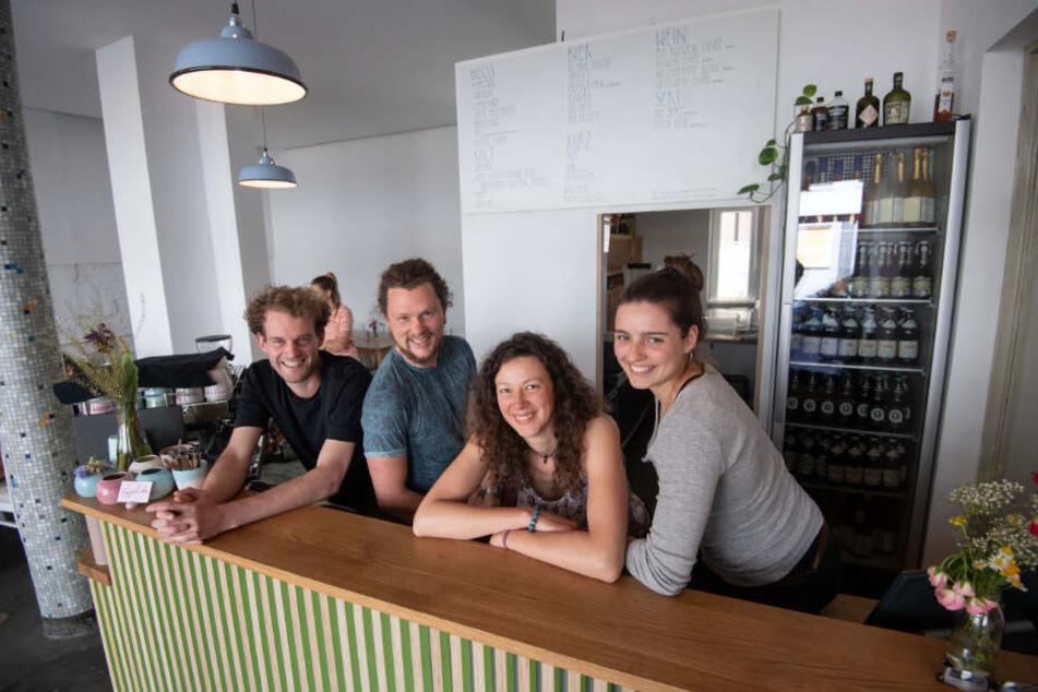"""Mitglieder des Gründerteams des Café """"Raupe Immersatt"""" stehen hinter der Theke ihres Cafés."""