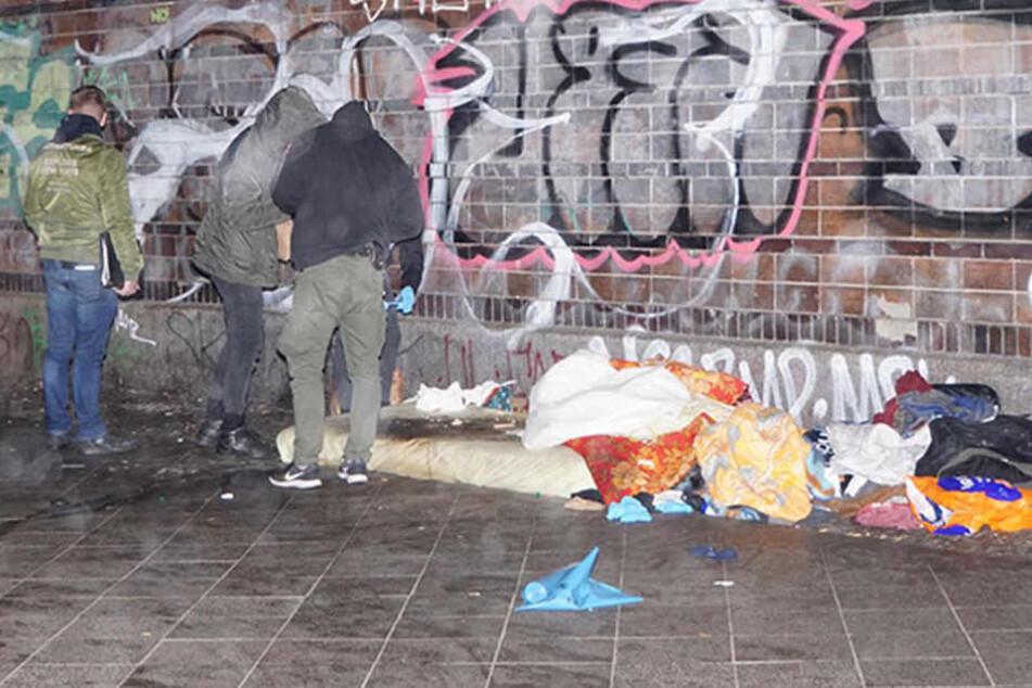 Beamte untersuchen den Schlafplatz des verstorbenen Mannes.