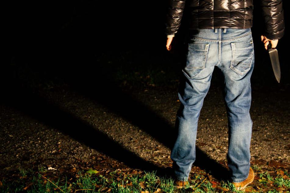 Ein Mann steht mit einem Messer in der Hand in der Dunkelheit. (Symbolbild)
