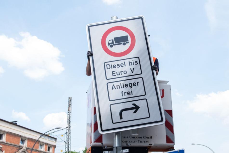 Ein Fahrverbotsschild für Lastwagen wird an der Max-Brauer-Allee aufgehängt.