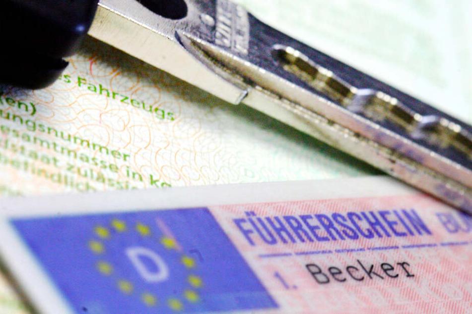Ein Führerschein und ein Autoschlüssel liegen auf einem Fahrzeugschein in Frankfurt am Main (Hessen).