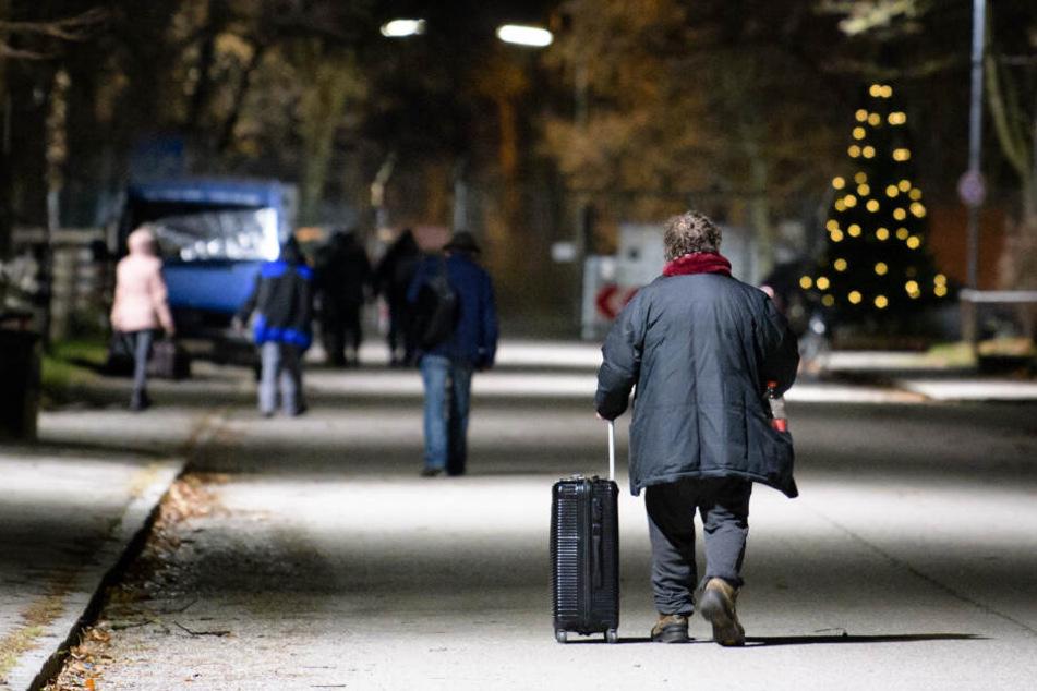 Obdachlose gehen über das Gelände der Bayernkaserne: Die Nachtunterkunft für Obdachlose wird während der Sprengarbeiten geräumt. (Archivbild)