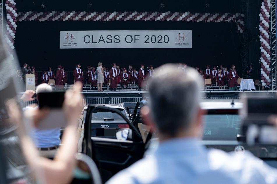 Angehörige der Absolventinnen und Absolventen der Internationalen Schule Hannover Region (ISHR) verfolgen und filmen im Autokino auf dem Schützenplatz die Abschlussfeier.