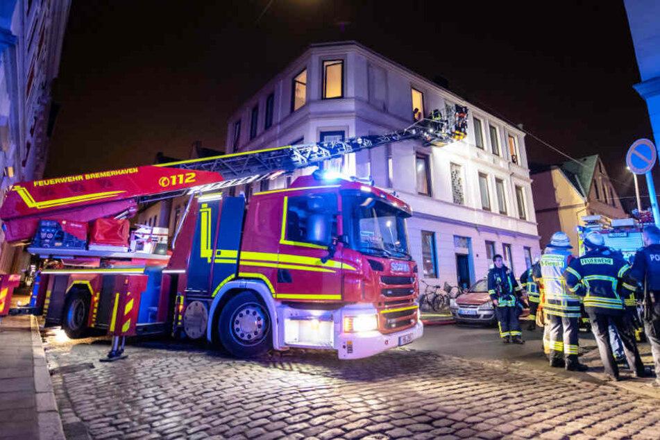 Feuerwehrleute löschen von einer Feuerwehrleiter aus einen Brand in einem Mehrfamilienhaus in Bremerhaven.