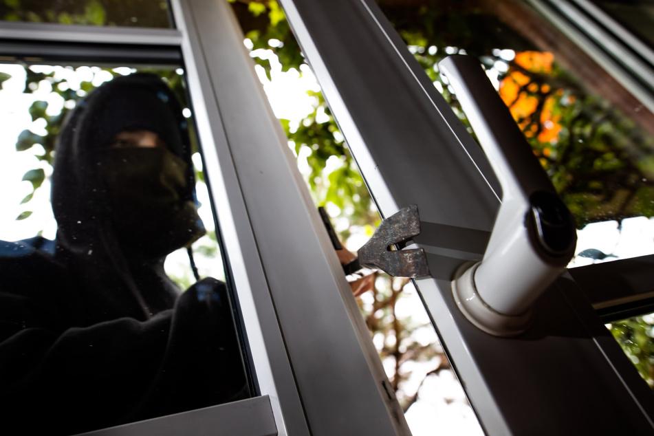Ein Einbrecher benutzt ein Brecheisen, um eine gekippte Terrassentür aufzuhebeln. (Symbolfoto)