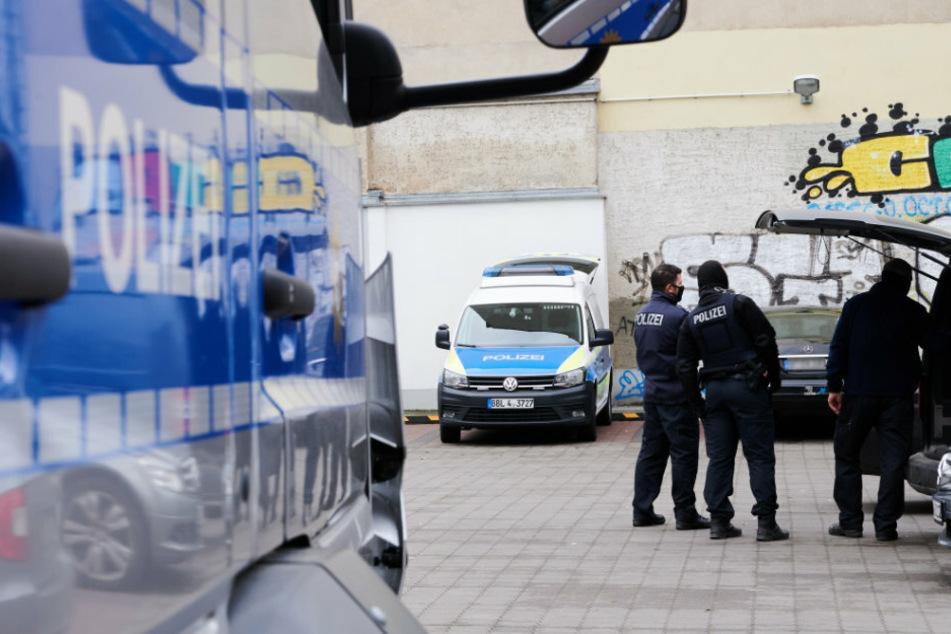 Ein Polizist steht bei einem Einsatz auf einem Parkplatz.