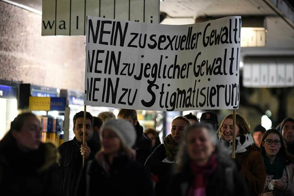 """Demonstranten halten ein Plakat mit der Aufschrift """"Nein zu sexueller Gewalt! Nein zu jeglicher Gewalt! Nein zu Stigmatisierung!""""."""