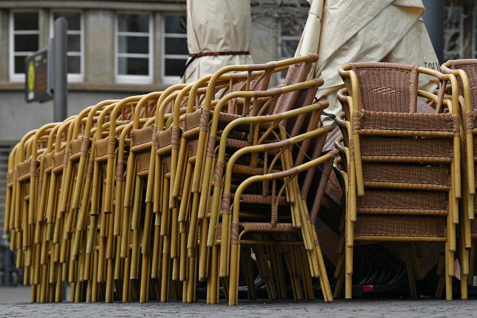 Übereinandergestapelt sind die Stühle vor einem Restaurant am Erfurter Fischmarkt. Sollte in Thüringer Landkreisen die Inzidenz unter 100 fallen, dürfte die Außengastronomie wieder öffnen.