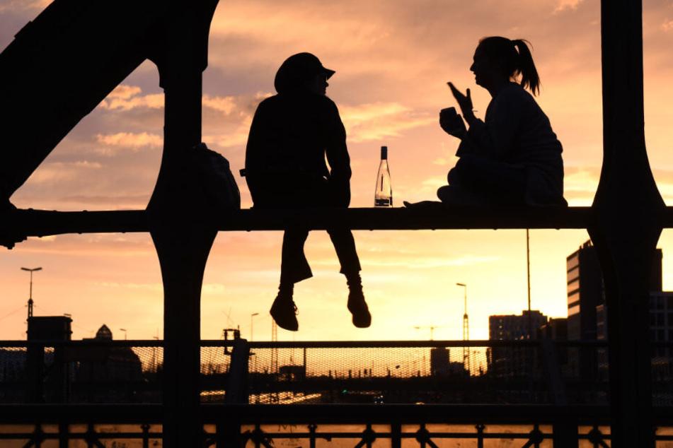 Zwei junge Frauen sitzen auf einem Stahlträger der Hackerbrücke und trinken während die Sonne unter geht. (Symbolbild)