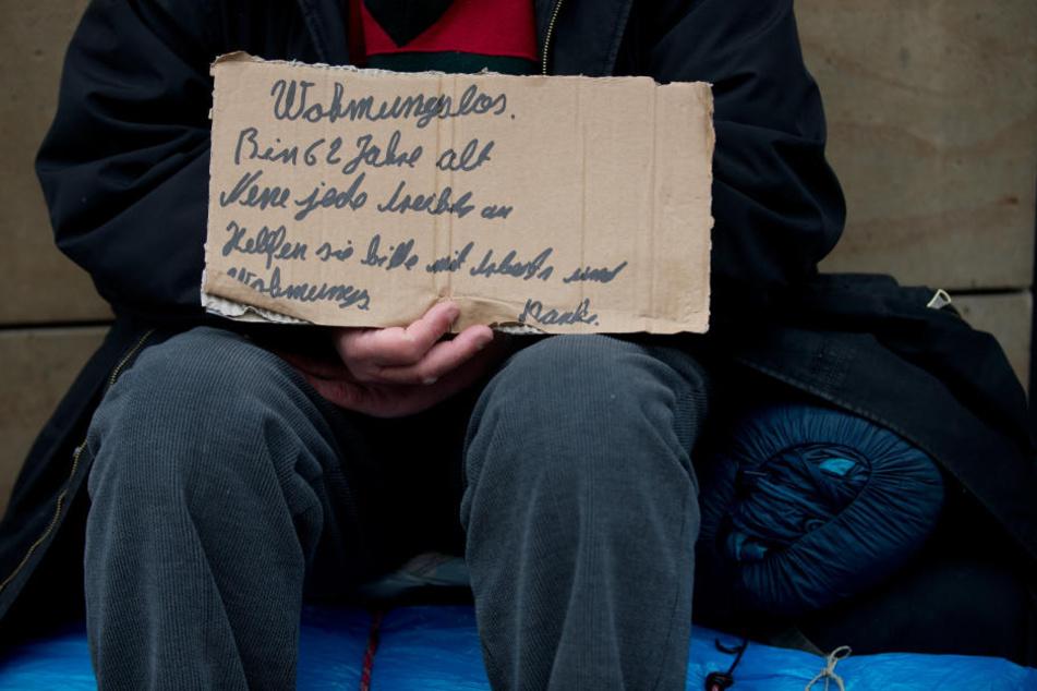 Ein Obdachloser hält auf der Königstraße in Stuttgart ein Pappschild mit der Bitte um Arbeit und eine Wohnung in den Händen. (Archivbild)
