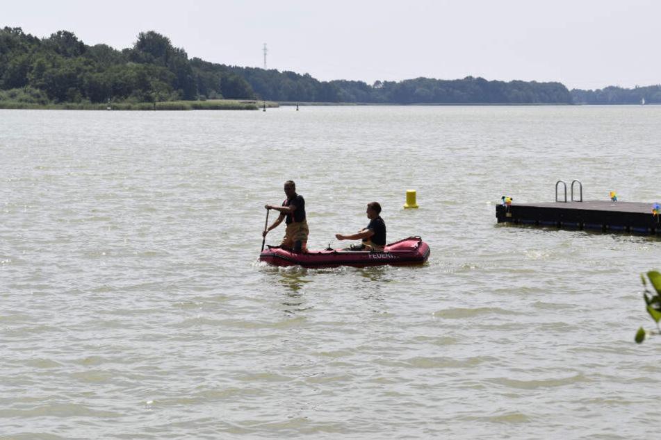 Einsatzkräfte der Feuerwehr sind mit einem Schlauchboot am Dienstag auf dem Ruppiner See unterwegs.