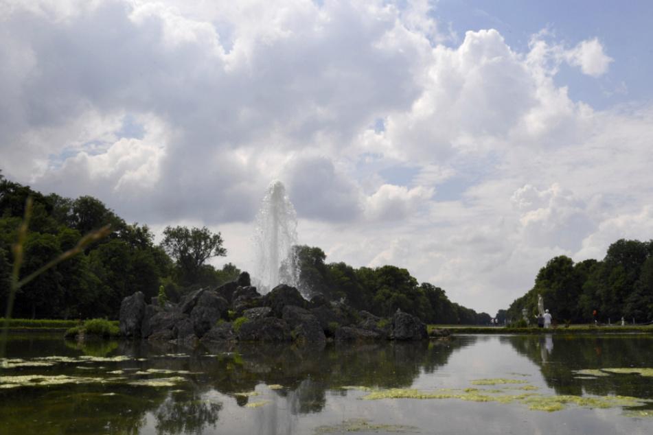 Die Fontäne eines Springbrunnens ist im Schlosspark Nymphenburg bei bewölktem Himmel und Sonne zu sehen.