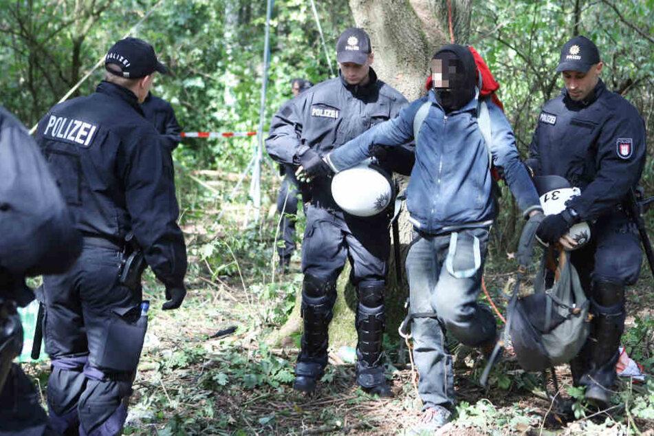 Zwei Polizisten führen einen Besetzer ab.