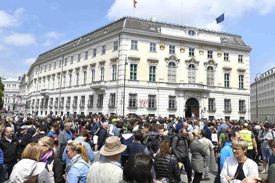 Menschen demonstrieren vor dem Bundeskanzleramt.