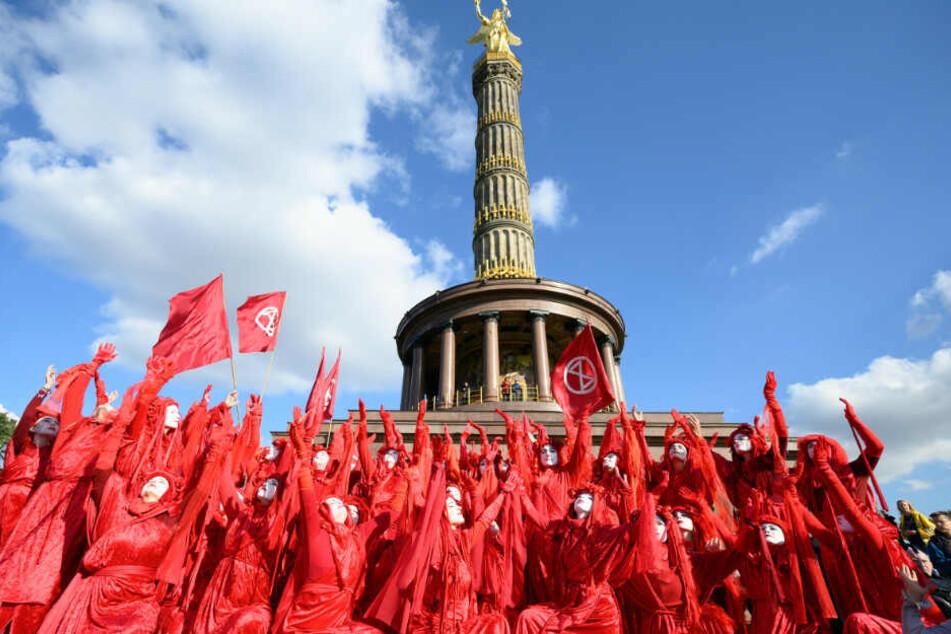"""Rot gekleidete Aktivisten der Klimabewegung """"Extinction Rebellion"""" führen zum Auftakt ihrer Aktionswoche """"Berlin blockieren"""" bei einer Blockade der Zufahrten zum Großen Stern an der Siegessäule eine Aufführung auf."""