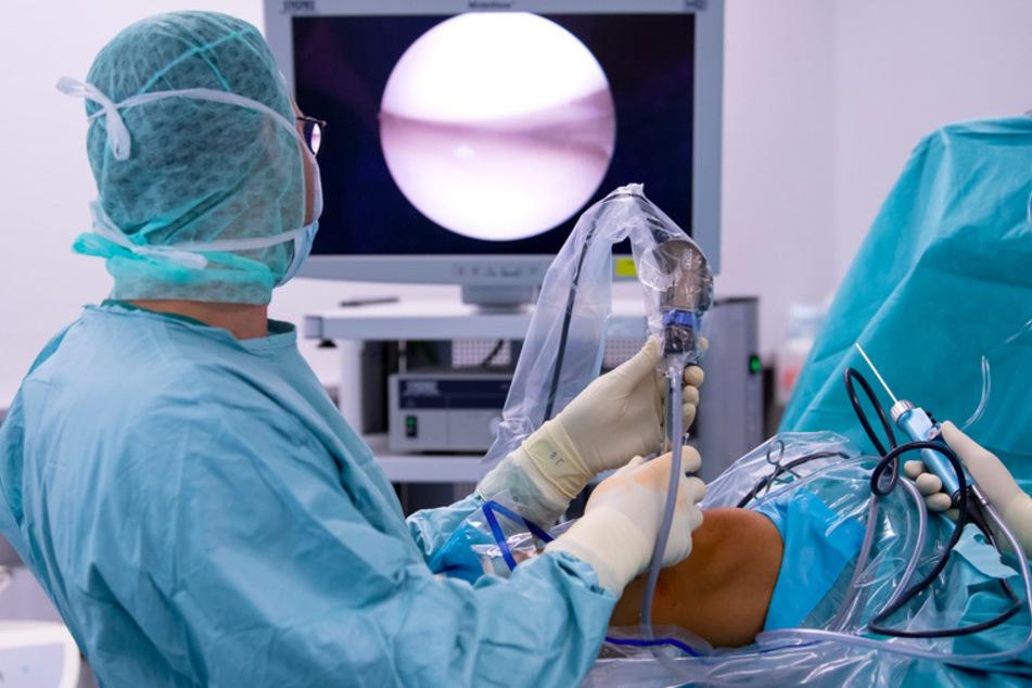 Ein Arzt operiert in der Orthopädischen Chirurgie München (OCM) einen Patienten am Knie.