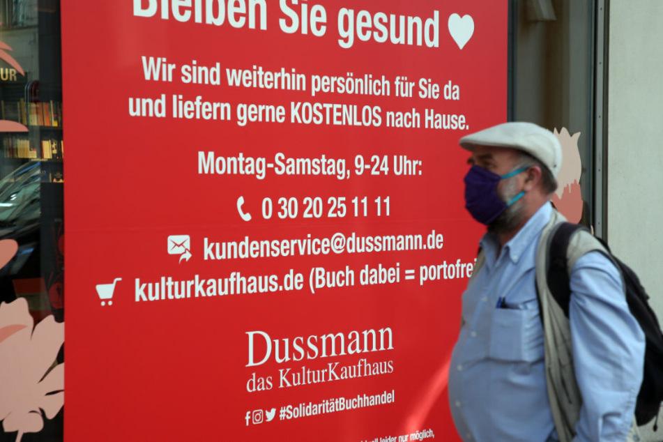 Ein Mann trägt einen Mundschutz und geht an einem Hinweisschild am für Kunden geschlossenen Kulturkaufhaus Dussmann in der Friedrichstraße vorbei.
