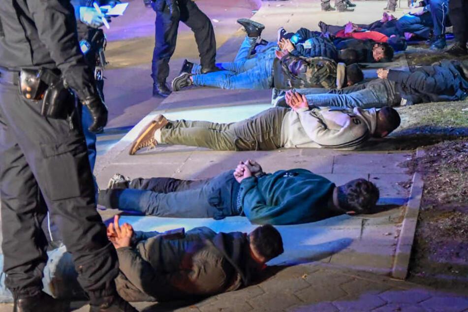 Mehrere verdächtige Männer liegen am Boden.
