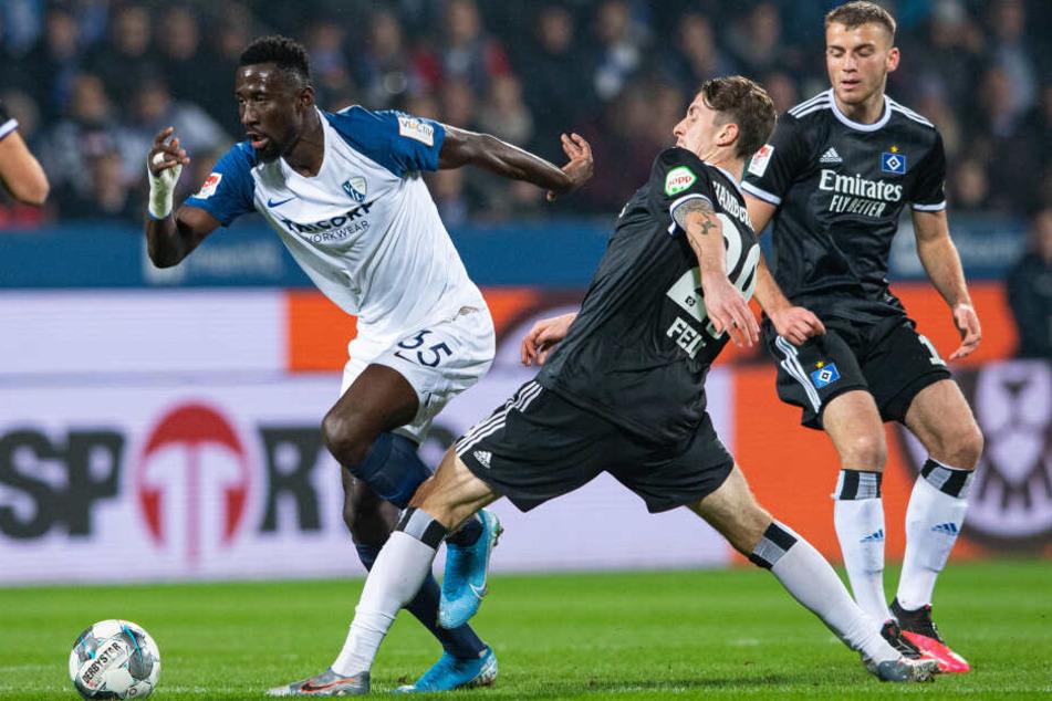 Hamburgs Adrian Fein (m) und Bochums Silvere Ganvoula (l) kämpfen um den Ball.