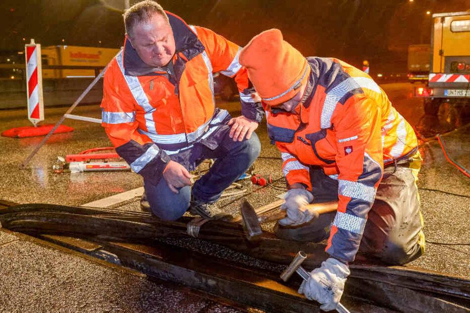 Zwei Baustellen-Mitarbeiter reparieren den Lamellen-Bruch auf der A7. (Archivbild)