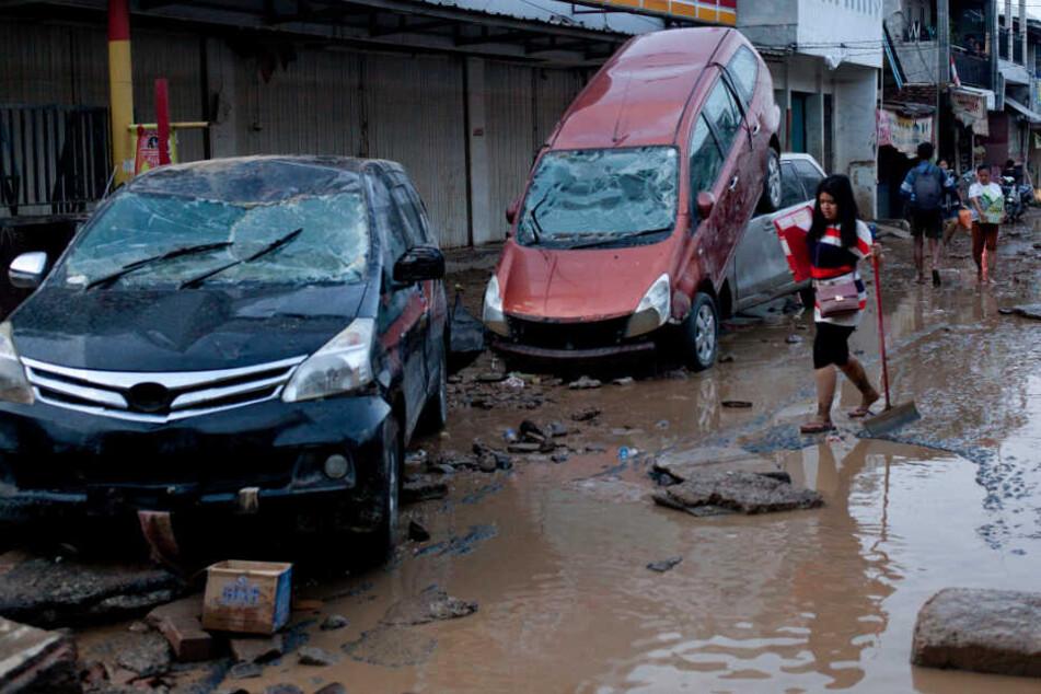 Ein Mädchen geht auf einer überschwemmten Straße an zerstörten Autos vorbei.