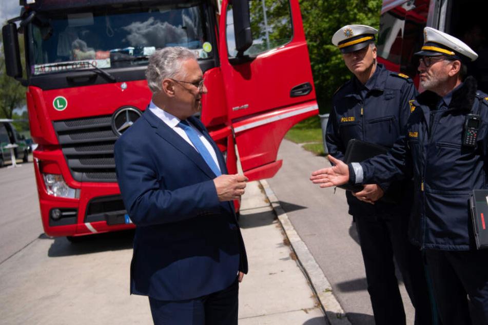 Joachim Herrmann (l, CSU), Innenminister von Bayern, besucht an der Autobahn 9 (A9) eine Lkw-Kontrollstelle und unterhält sich mit Polizisten.