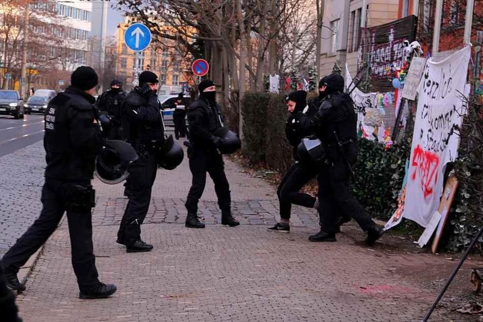 Eine Aktivistin wird von Polizisten abgeführt.