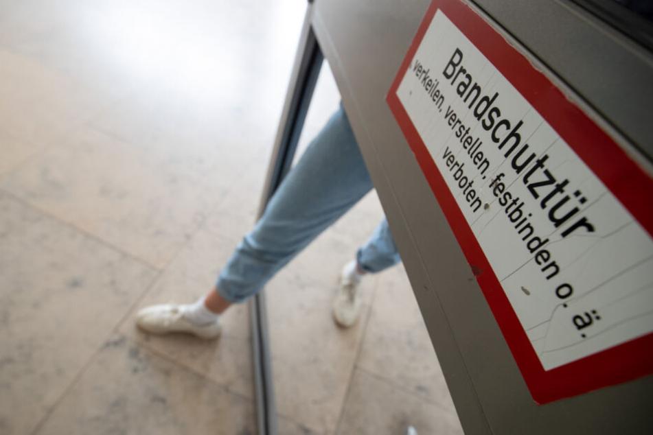 Eine Studentin steigt in einem Gebäude am FAU-Campus an der Regensburger Straße mit ihrem Fuß durch ein Loch einer defekten Brandschutztür.