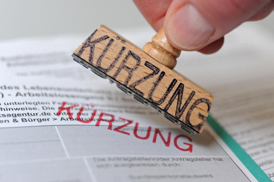 """Ein Mann hält einen Stempel, auf dem das Wort """"Kürzung"""" steht, über ein Formular zur Beantragung von Arbeitslosengeld II (Hartz-IV)."""