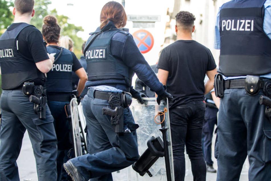 Polizisten bewachen am frühen Morgen eine Gruppe festgesetzter junger Männer neben dem Herrngarten am Rande der Innenstadt.