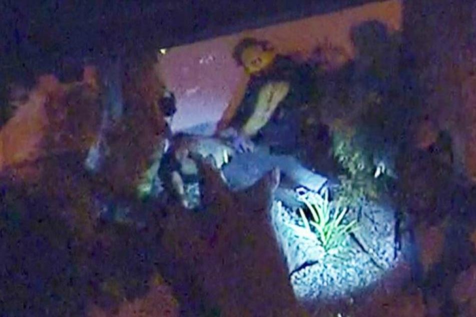 Video zeigt Beamte, die sich nahe einer Bar, in der mehrere Schüsse gefallen sind, über eine Person am Boden beugen.