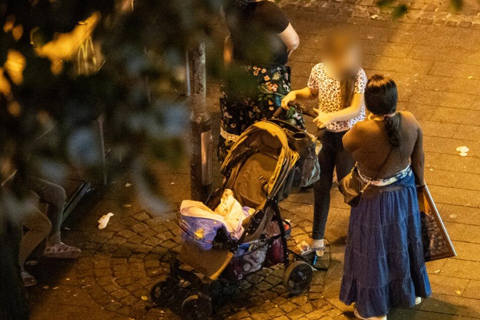 Bettelnd ziehen Frauen mit ihren Kindern nachts über die Kaiserstraße im Bahnhofsviertel von Frankfurt.