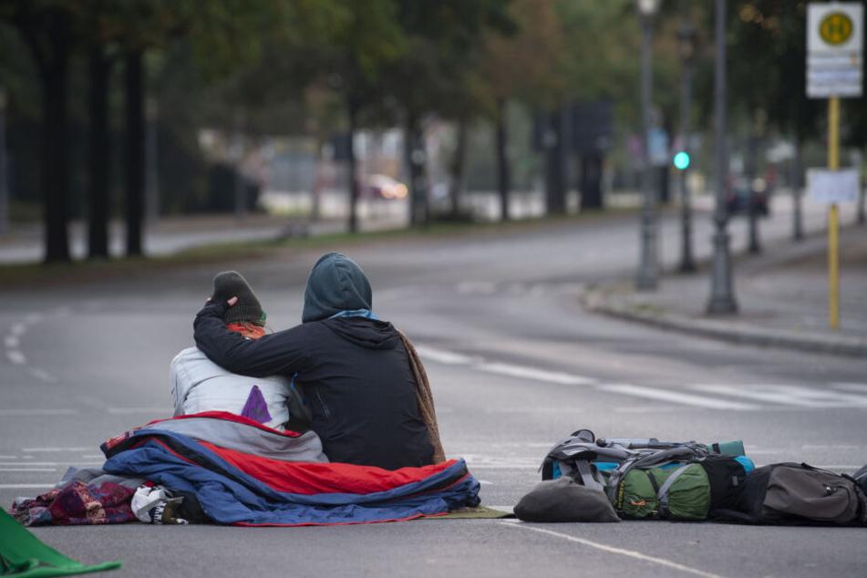 Klima-Aktivisten haben die Zufahrten zum Großen Stern blockiert. Dieses Pärchen sitzt auf der Straße, die zum Schloß Bellevue führt.