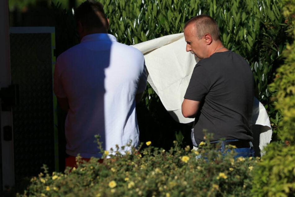 Polizeibeamte bringen den Tatverdächtigen aus dem Haus.