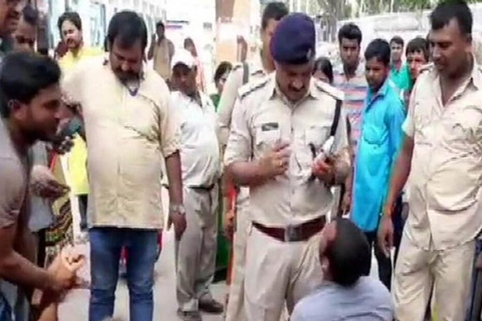 Polizisten vernehmen einen Dorfbewohner.