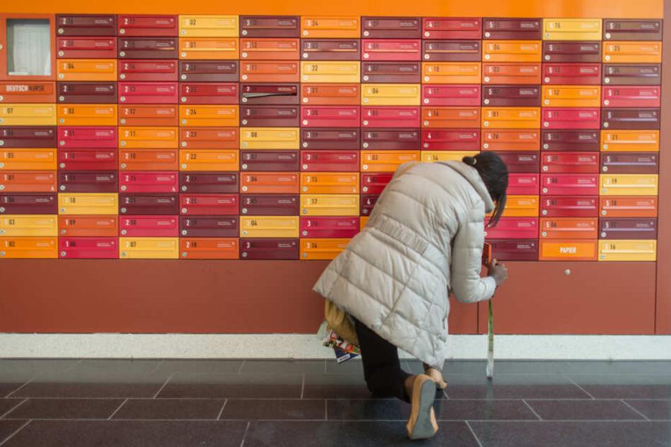 Eine Studentin leert ihren Briefkasten im Eingangsbereich des Studentenwohnheims Agnes-/Adelheidstraße in München.