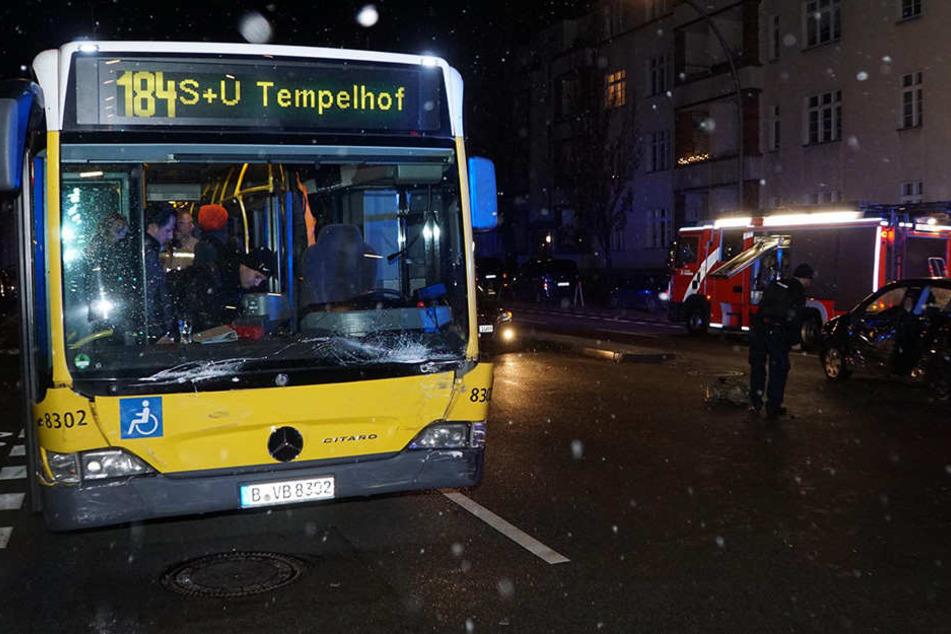 Polizisten und Feuerwehr betrachten den Schaden am Bus und PKW.