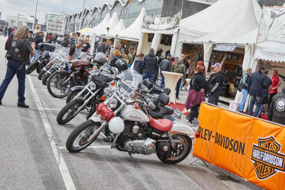 """Besucher der """"Harley Days"""" betrachten die zur Schau gestellten Motorräder."""